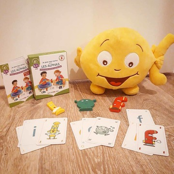 """[MARDI PÉDAGOGIE]  La semaine dernière, nous vous avons présenté la nouvelle édition de l'ouvrage """"La Transformation des Alphas"""". Place aujourd'hui à notre nouveau jeu de cartes !  """"Je joue aux cartes avec les Alphas"""" est un outil indispensable en complément de cet ouvrage, afin de faire le lien entre les Alphas et les Alphas transformés.  Il va permettre aux enfants de s'entraîner à associer les Alphas à leurs nouvelles apparences, grâce à 3 types de cartes : celles à dos orange avec les Alphas, celles à dos bleu avec l'écriture minuscule scripte, et celles à dos jaune avec l'écriture majuscule scripte.  Ce jeu de cartes va aider les enfants à s'approprier les différents types d'écriture : en reconnaissant les Alphas sous leurs nouvelles apparences, la minuscule et la majuscule scriptes, types d'écriture utilisés pour apprendre à lire, les enfants vont pouvoir assimiler que les Alphas sont présents dans les livres sous d'autres formes que celles qu'ils connaissent, et pourront ainsi lire leurs premiers textes.  Grâce à un livret de jeu, les adultes auront l'occasion de mettre en place des jeux de correspondance entre les Alphas et les différents types d'écriture, en commençant par la reconnaissance des Alphas de la famille des voyelles, puis ceux représentant les consonnes longues et les consonnes courtes, comme conseillé pour suivre la progression de la méthode, et d'abord l'introduction de la minuscule scripte avant la majuscule, afin de suivre le rythme des enfants.  *Vous avez peut-être déjà """"Mon jeu des cartes des Alphas"""" ? Notre nouveau jeu, """"Je joue aux cartes avec les Alphas"""" est un jeu simplifié au sens où il ne contient pas la minuscule et majuscule cursives, présentes dans notre premier jeu de cartes, afin de se concentrer uniquement sur les lettres utilisées pour apprendre à lire.  #lesalphasofficiel #lesalphas #methode #lecture #recrealire #edition #pedagogie #apprentissage #enfants #lire #lettres #transformation #activites #cartes #jeu #minuscule #maj"""